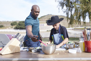 Host Eddie Jackson with contestant Ty Machado, as he prepares his dish for the Chicken BBQ Challenge, as seen on Food Network's Kids BBQ Challenge Season 1.